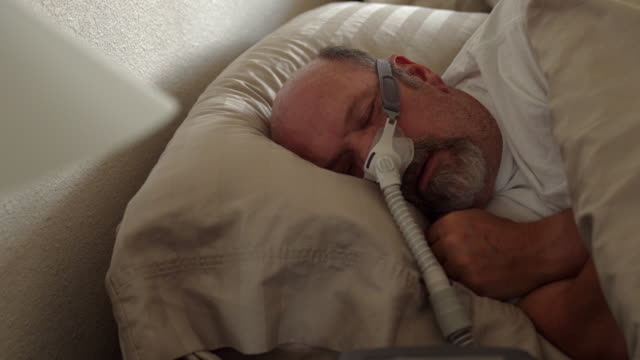 middle aged man with sleep apnea asleep in a bed wearing a cpap (continuous positive airway pressure) machine to aid in his sleeping - sleep apnea stock videos and b-roll footage