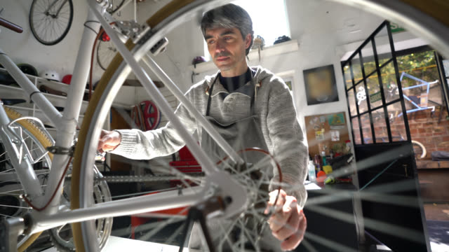 Middle aged man working at a bicycle repair shop fixing a bicycle and spinning the back wheel looking very focused