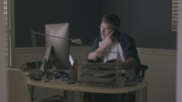 stockvideo's en b-roll-footage met middle aged man working from home office on video call. - koffiekop