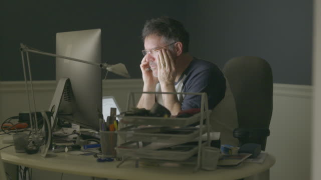 stockvideo's en b-roll-footage met middle aged man working from home office on video call. - uitgeput