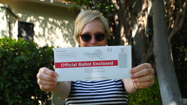 middle aged woman holds up her vote by mail envelope - voting ballot stock videos & royalty-free footage
