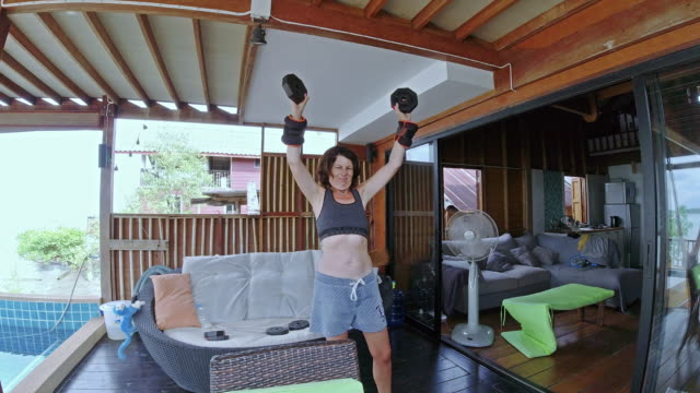 middle aged woman home exercising weight training timelapse - hand weight stock videos & royalty-free footage
