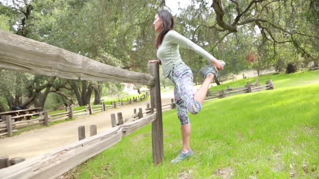 middle aged woman in park stretching before a run - only mature women stock videos & royalty-free footage