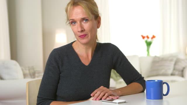 vídeos de stock e filmes b-roll de middle aged woman laughing and talking to camera - só uma mulher madura