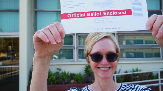 vídeos de stock e filmes b-roll de middle aged woman mailing her absentee voter ballot - correios