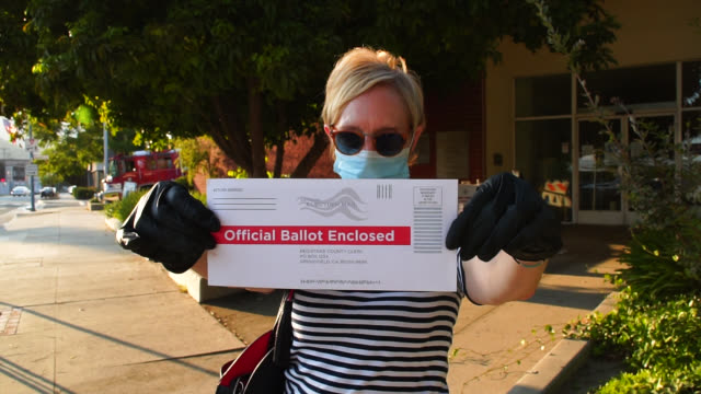 middle aged woman mailing her absentee voter ballot - voting ballot stock videos & royalty-free footage