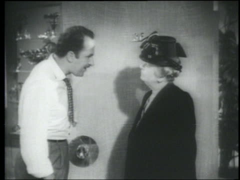 B/W 1948 middle aged woman + man (Keenan Wynn) talking; woman slaps man + walks away
