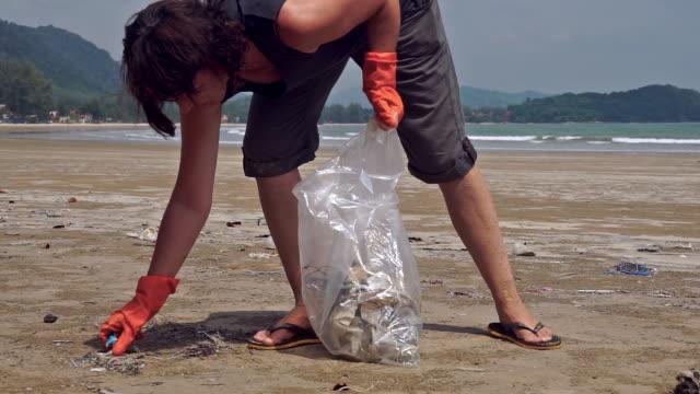 medelålders kvinna plocka upp plast skräp förorening på stranden volontär miljösanering - slit och släng bildbanksvideor och videomaterial från bakom kulisserna