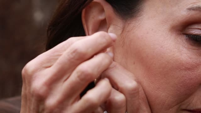 middle aged woman putting on earring - earring stock videos and b-roll footage