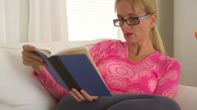 Middle Aged woman reading book in living room