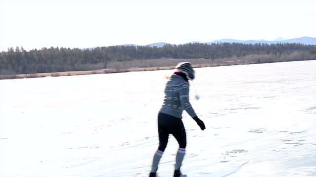Middle aged woman skates on frozen lake