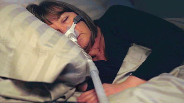 middle aged woman sleeping soundly using a cpap machine to cure her sleep apnea - pillow stock videos & royalty-free footage