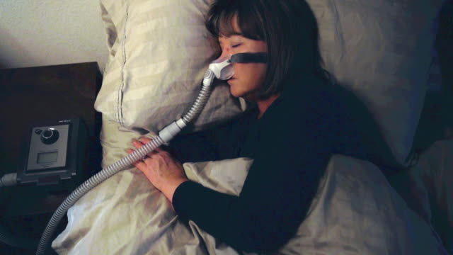 middle aged woman sleeping soundly using a cpap machine to cure her sleep apnea - overweight patient stock videos & royalty-free footage