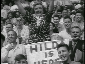 vidéos et rushes de middle aged woman standing + cheering at ebbets field / brooklyn, ny / newsreel - 1947