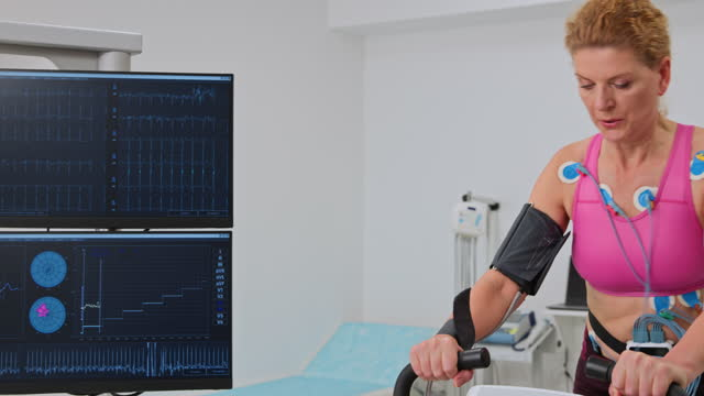 pan middle aged woman taking a cardio stress test by riding a bicycle ergometer - 50 54 years stock videos & royalty-free footage