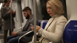 middle aged woman traveling in metro car