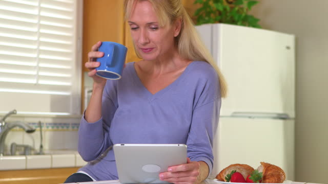 Middle Aged woman using tablet and drinking coffee