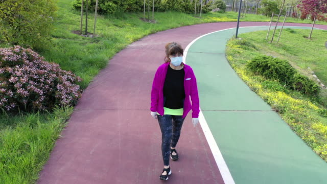 vídeos de stock e filmes b-roll de middle aged woman walking in the park wearing protective masks during the covid-19 outbreak - treinar