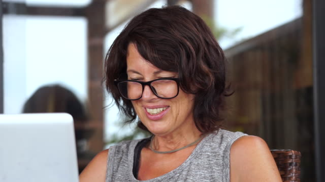 middle aged woman with glasses ending computer video call from garden - casual clothing stock videos & royalty-free footage