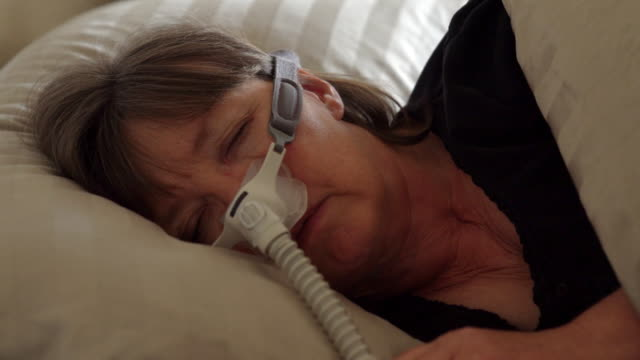 middle aged woman with sleep apnea asleep in a bed wearing a cpap (continuous positive airway pressure) machine to aid in her sleeping - sleep apnea stock videos and b-roll footage