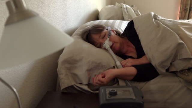 middle aged woman with sleep apnea asleep in a bed wearing a cpap (continuous positive airway pressure) machine to aid in her sleeping - inhaling stock videos & royalty-free footage