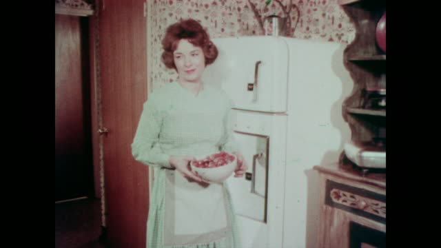 vidéos et rushes de 1967 middle class american housewife removes spoiled strawberries from the refrigerator and puts them in the trash - aliments et boissons