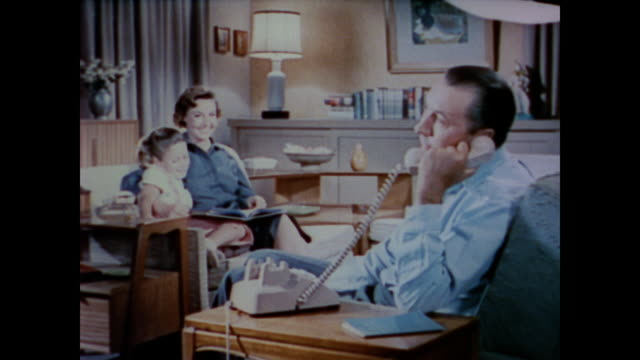 1958 a middle class wife and daughter sit on the couch smiling as a happy father talks on the telephone - landline phone stock videos & royalty-free footage