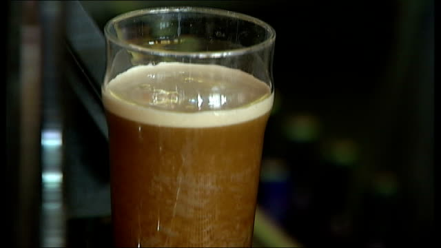 middle class wine drinkers could be risking their health; two men clinking pint glasses bar staff at work close shot of pint of guinness settling... - middle class stock videos & royalty-free footage