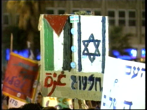 peace initiative; itn israel: ext/night mass demo with huge benner 'peace now' pull out thousands more peace demos with banners and singing heard sof... - itv late evening bulletin点の映像素材/bロール