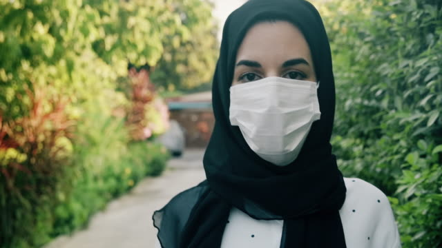 middle east woman wearing medical mask, to protect from virus, walking on the street. - surgical mask stock videos & royalty-free footage