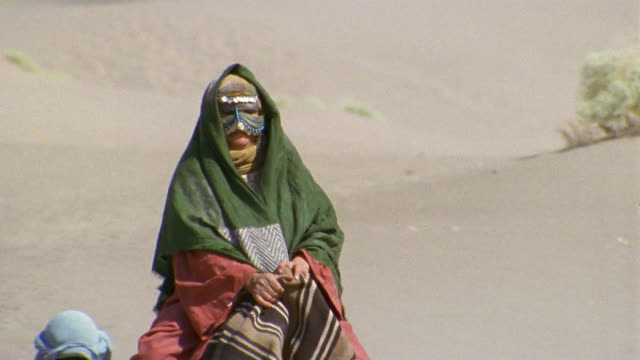 cu, middle east, woman with mask on face riding camel in desert, tu - ベドウィン族点の映像素材/bロール