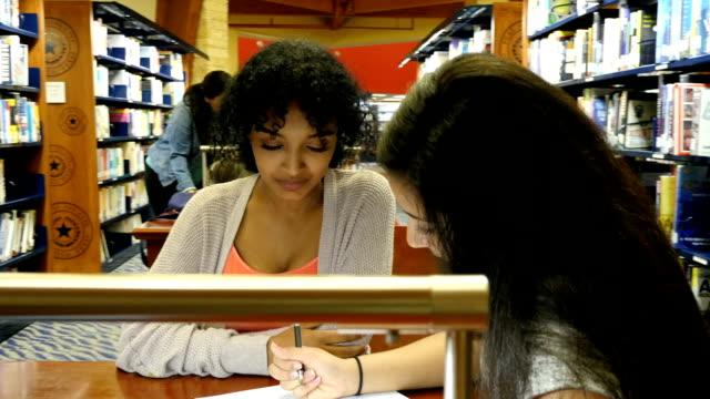 中東とアフリカ系アメリカ人女性の学生の学校のプロジェクトをブレインストーミングする。 - note pad点の映像素材/bロール