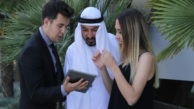 middle eastern businessmen and businesswoman working with digital tablet outdoor - business relationship stock videos & royalty-free footage