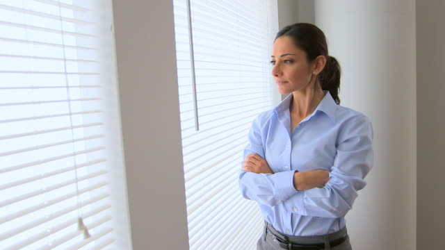Middle Eastern Businesswoman standing by window