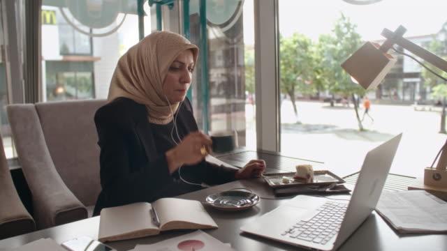 vidéos et rushes de middle eastern businesswoman video conferencing in cafe - hot desking