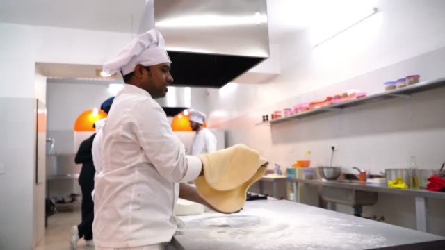 Middle eastern chef making a pizza throwing the dough up high