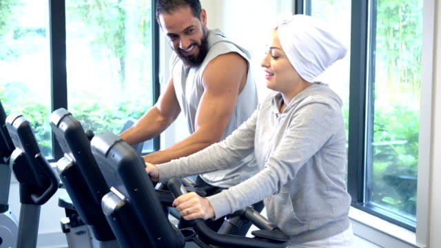 middle eastern couple exercising at the gym on bikes - exercise bike stock videos & royalty-free footage