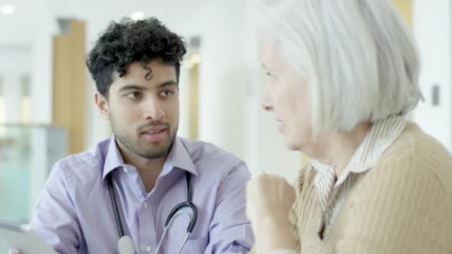 vídeos y material grabado en eventos de stock de médico de oriente medio hablando con paciente mayor femenina - azúcar