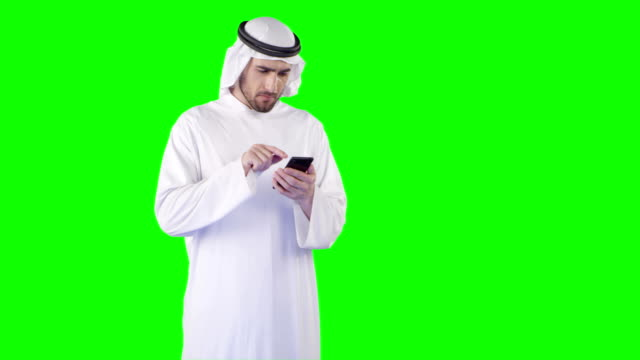 middle eastern ethnicity man using smart phone on green screen. alpha, loopable - middle eastern ethnicity stock videos & royalty-free footage