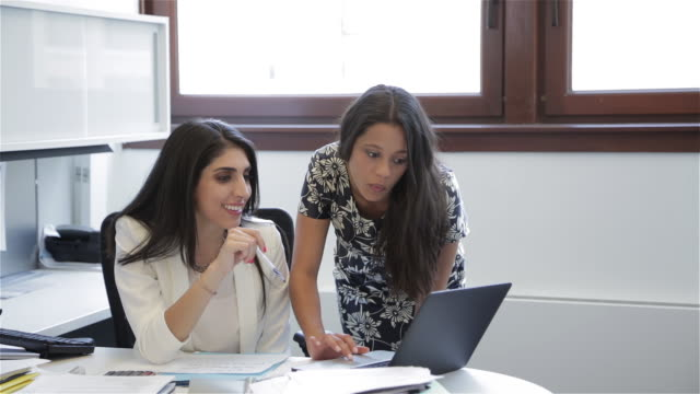 Middle Eastern female executive and African American female colleague look at ideas on a laptop