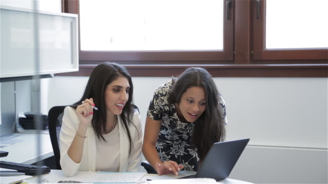 Middle Eastern female executive and African American female colleague work together on a laptop