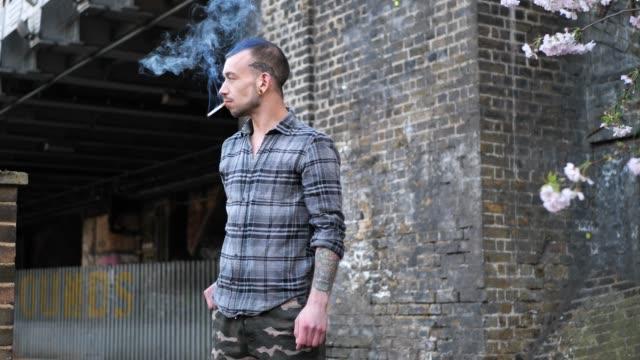vídeos de stock e filmes b-roll de middle eastern guy with tattoos, smoking a cigarette in the street - tatuagem