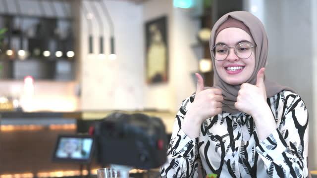 middle eastern influencer aufnahme ihres vlogs in einem cafe - content stock-videos und b-roll-filmmaterial