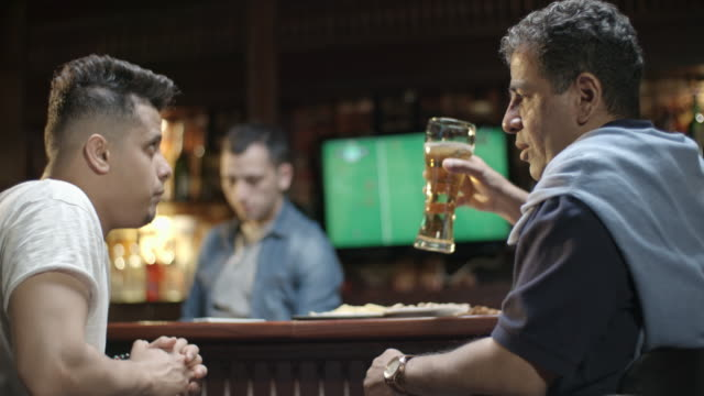 Middle eastern man drinking beer and speaking with son in bar