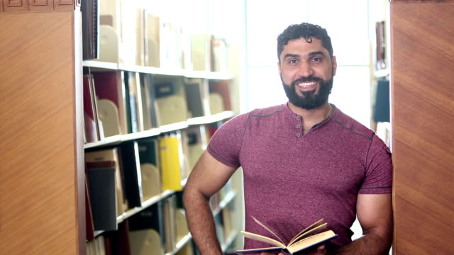 middle eastern man in library walks up to camera - approaching stock videos & royalty-free footage