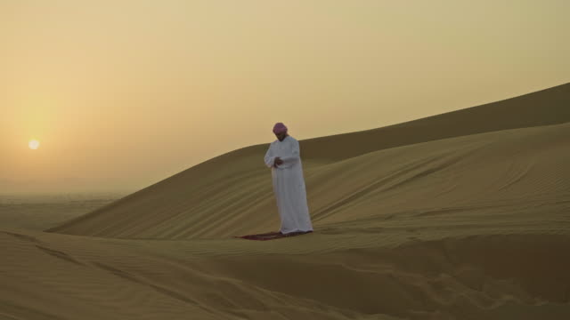 middle eastern man praying at sunrise in the desert - saudi arabia stock videos & royalty-free footage