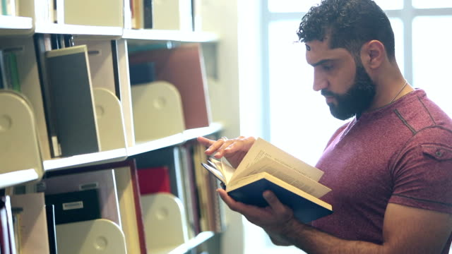middle eastern man standing in library reading book - library stock videos and b-roll footage