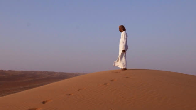 Middle Eastern man standing on top of desert dunes