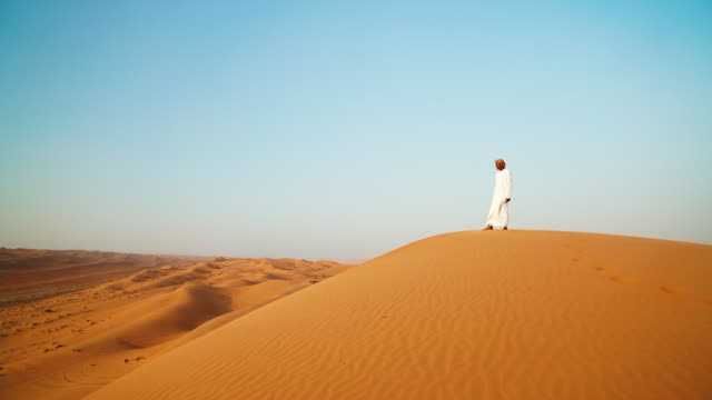 Middle Eastern man stands on top of dune in desert