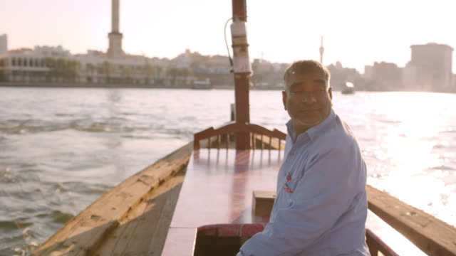 Middle eastern man takes solo trip along Dubai Creek at sunset